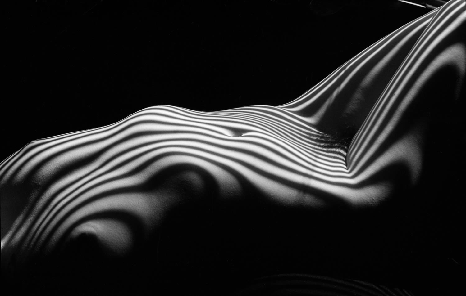 body lying down, zebra striped nude, photography by lucien clergue